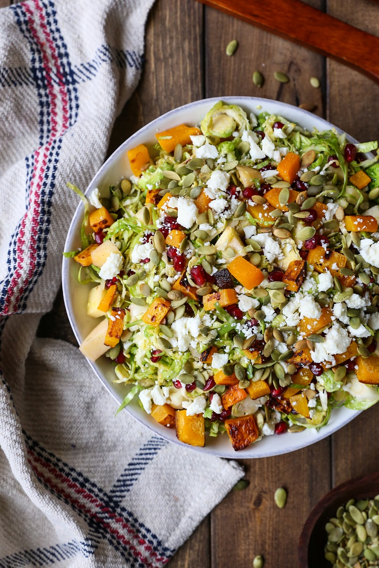 Shaved Brussel Sprout Salad with Roasted Butternut Squash, Pomegranate Seeds, Pumpkin Seeds, Feta, and Citrusy Maple Cinnamon Dressing | TheRoastedRoot.net #healthy #salad #vegetarian #gltuenfree #sidedish #thanksgiving